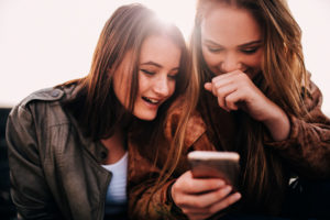 Teenage Girls Looking At Funny Photos On Smartphone And Laughing T20 G8VNKb 300x200